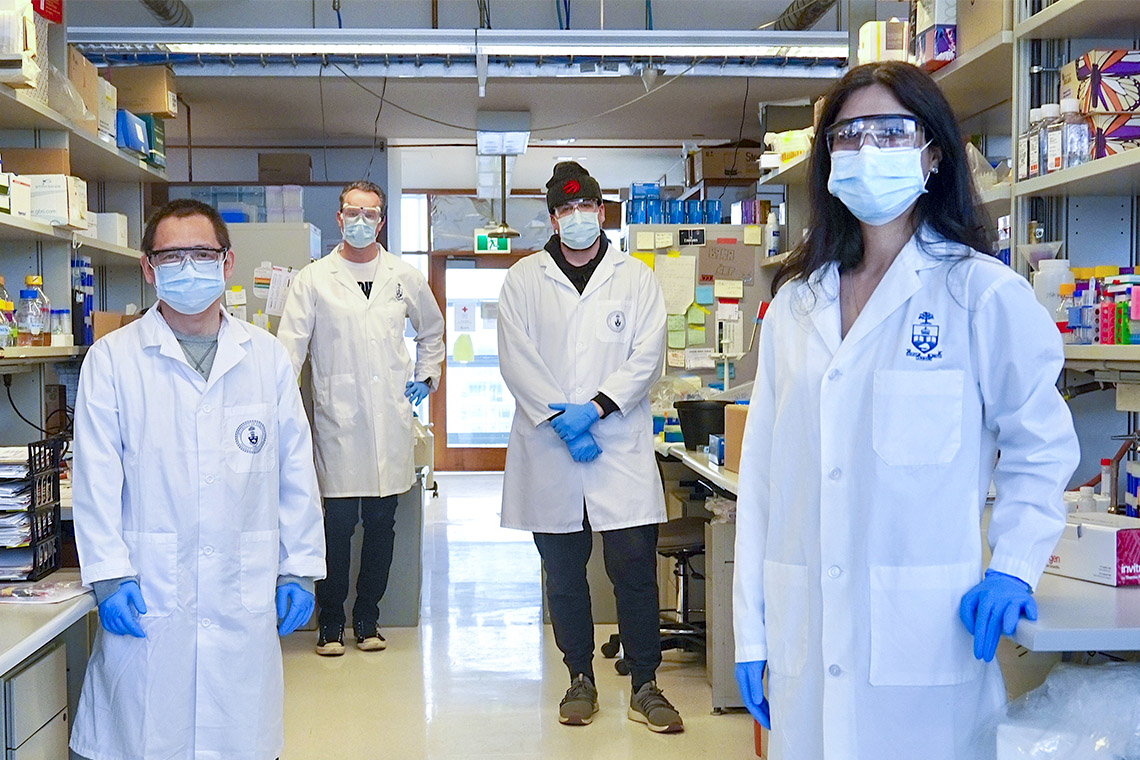 U of T researchers stand two metres apart in a lab, wearing lab coats and masks