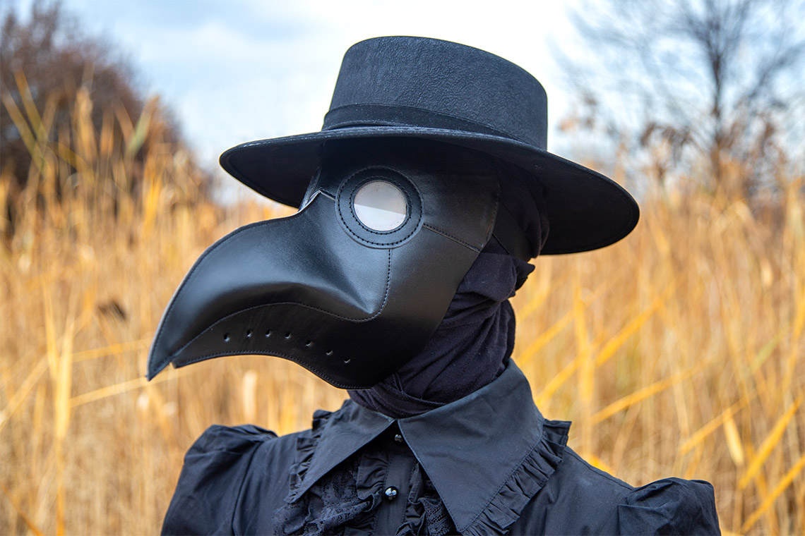 Madeleine Mant wears a plague doctor mask