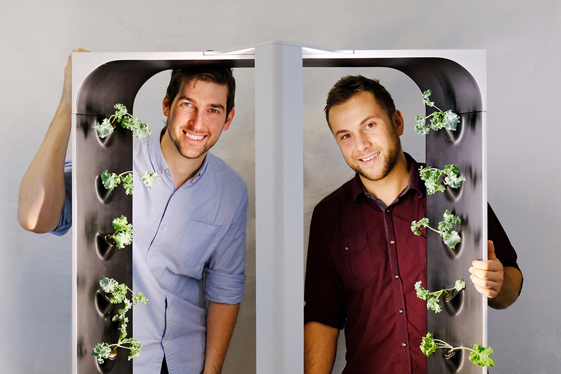 Conner Tidd and Kevin Jakiela are pictured looking through one of their hydroponic growing towers