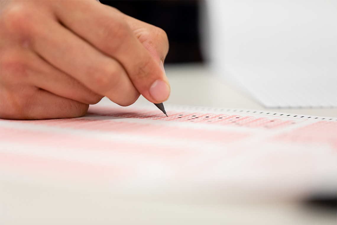Close up photo of a hand holding a pen above a multiple choice test sheet