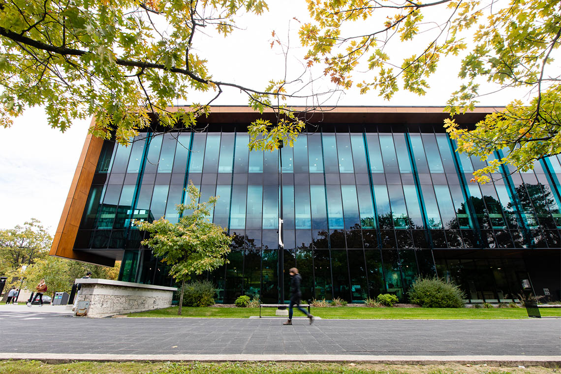 A student walks by a building on the U of T Mississauga campus