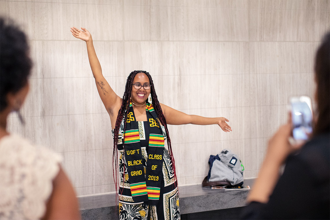 Sarah Edo wears a ceremonial scarf and poses for a photo after the 2019 black graduation ceremony