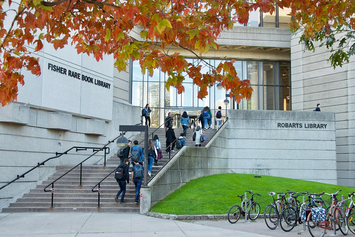 Students walk into Robarts Library with a tree in the foreground