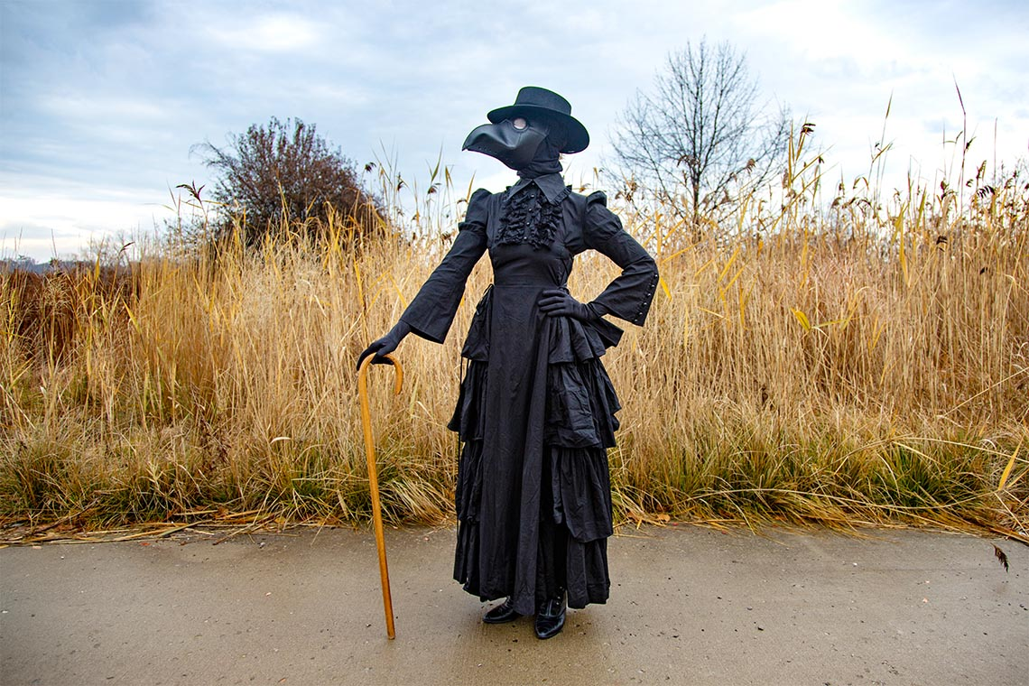 Madeleine Mant in costume as a plague doctor. The leather mask resembles the face of a black bird