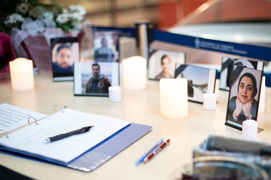 A condolence book for the victims of the PS752 plane crash is in the foreground with photos of the U of T victims in the background