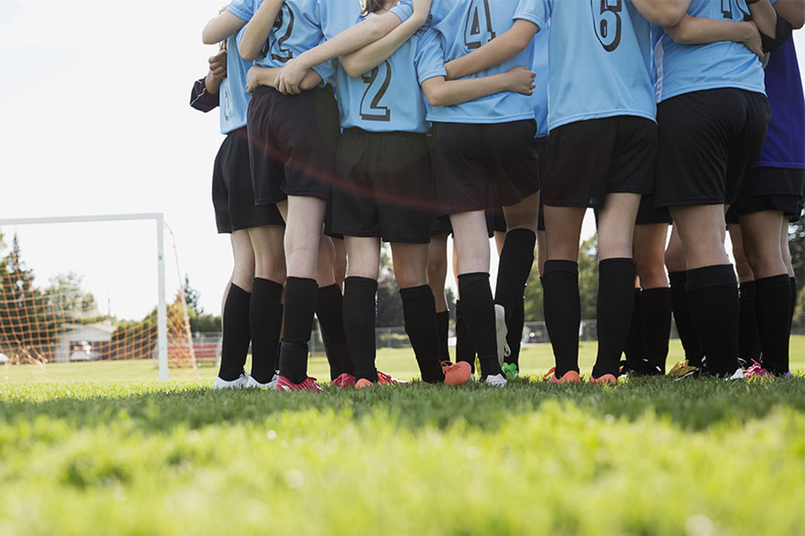 A group of young women in a huddle together on a soccer pitch