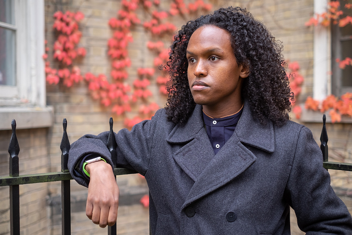 A photo of Egag Egag wearing a wool top coat leaning on a wrought iron fence with red ivy in the background