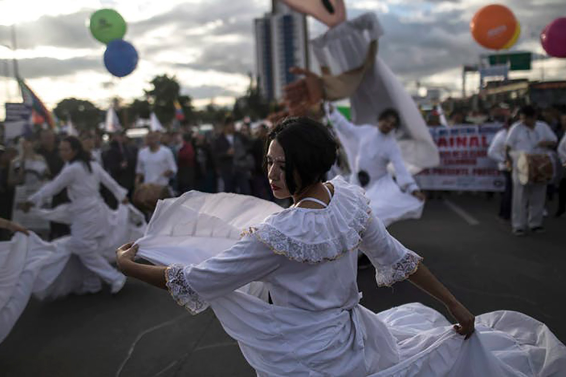 Photo of woman dancing during a protest march in Bogota