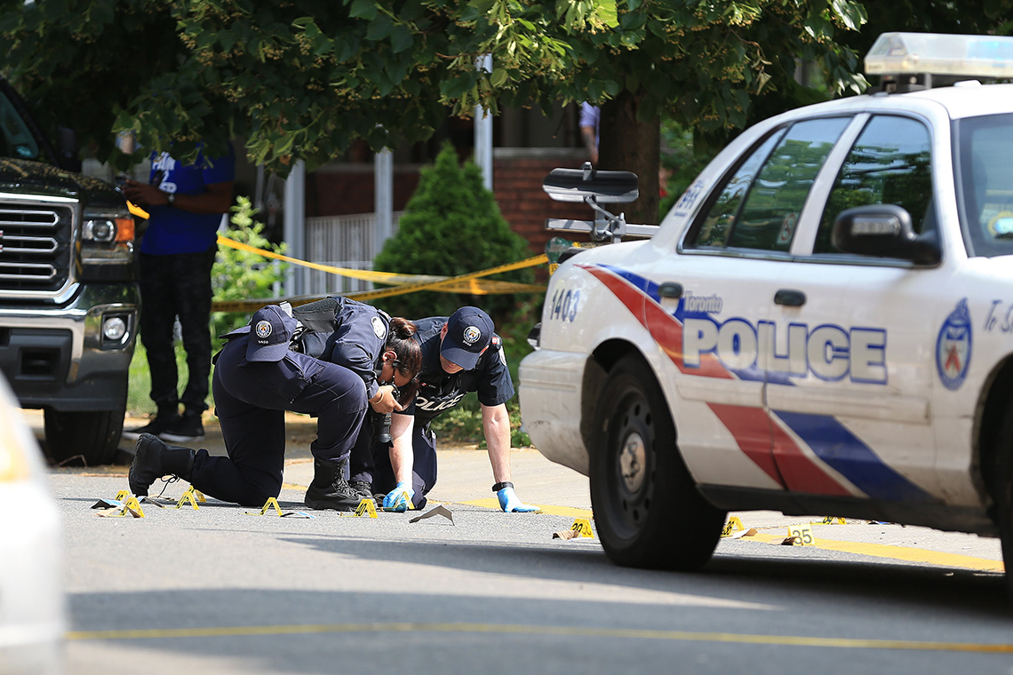 Photo of Toronto police examining shells and blood stains on street after shooting