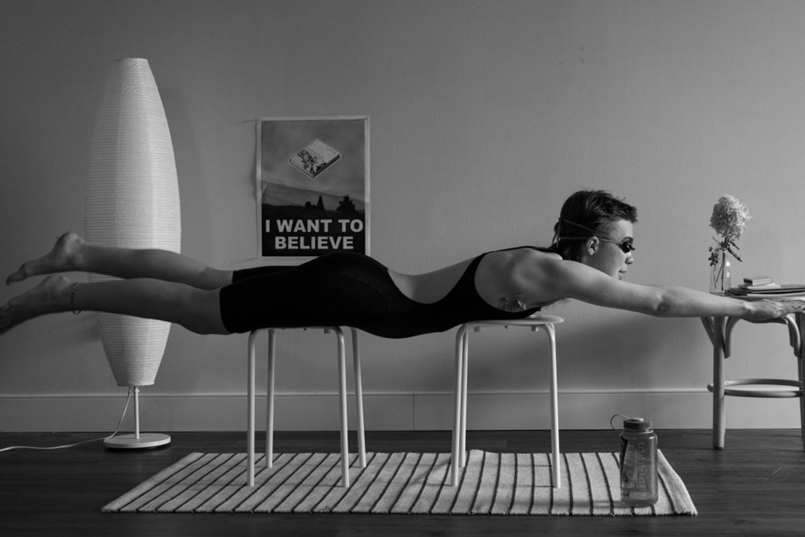 Person in a living room set on top of chairs in a horizontal position practicing swimming