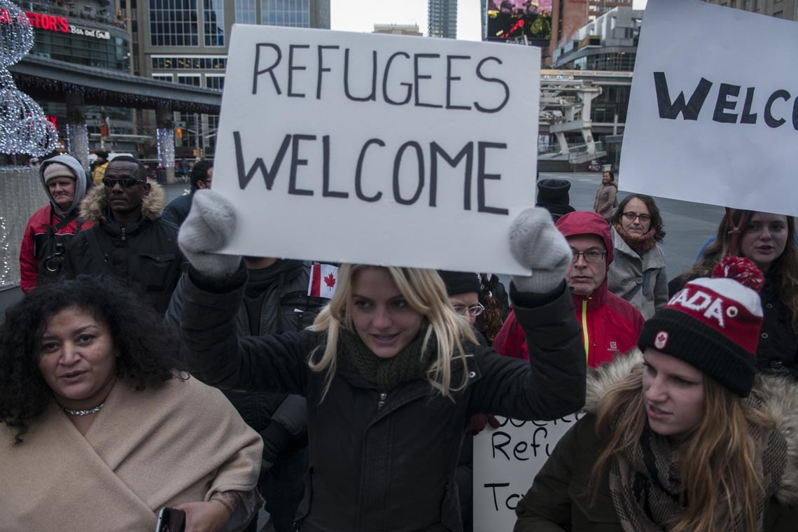 """Woman holding a sign saying """"Refugees Welcome"""" at rally in Toronto"""