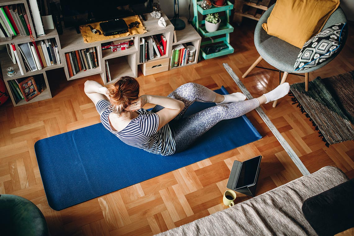 woman doing crunches on a yoga mat in her living room with tablet beside