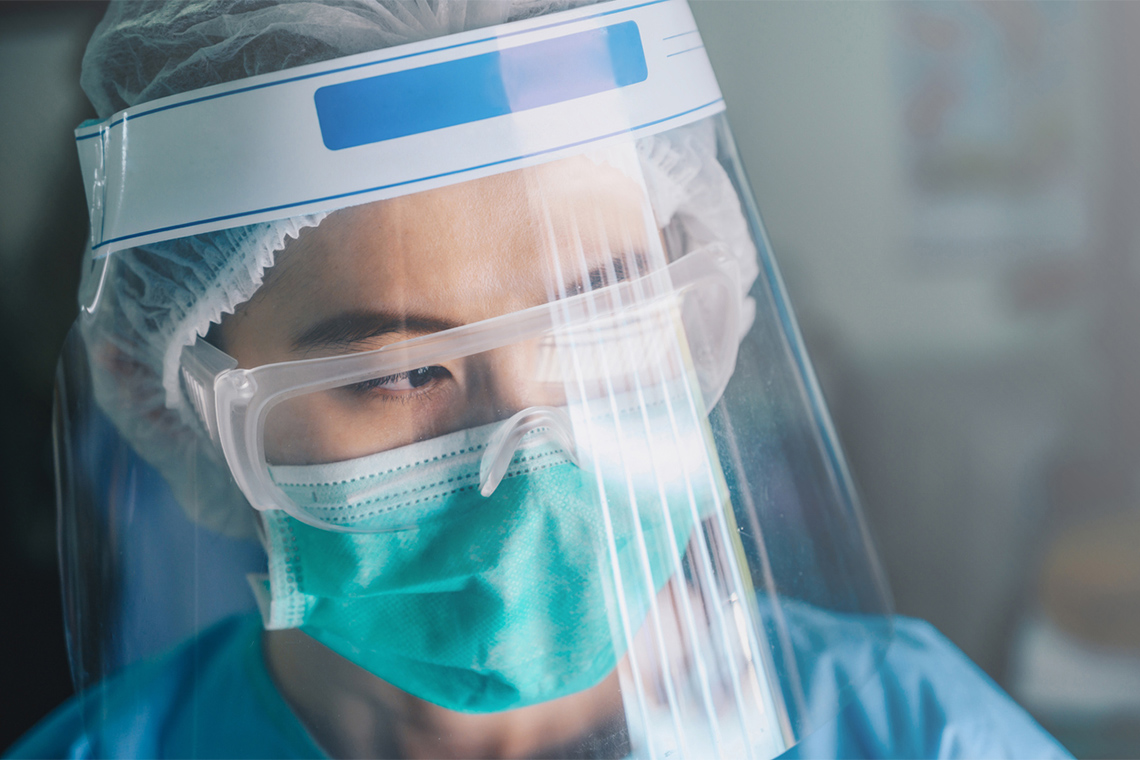 asian female nurse wearing multiple layers of PPE looking serious