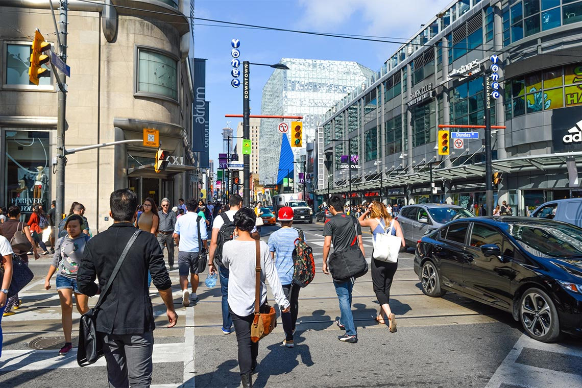 Pedestrians crossing a busy intersection near Dundas Square on Queen Street, in Toronto