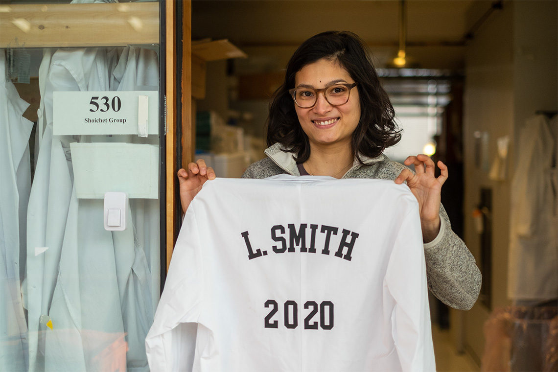 Laura Smith holds up a lab coat with her name and the planned year of her PhD thesis defence