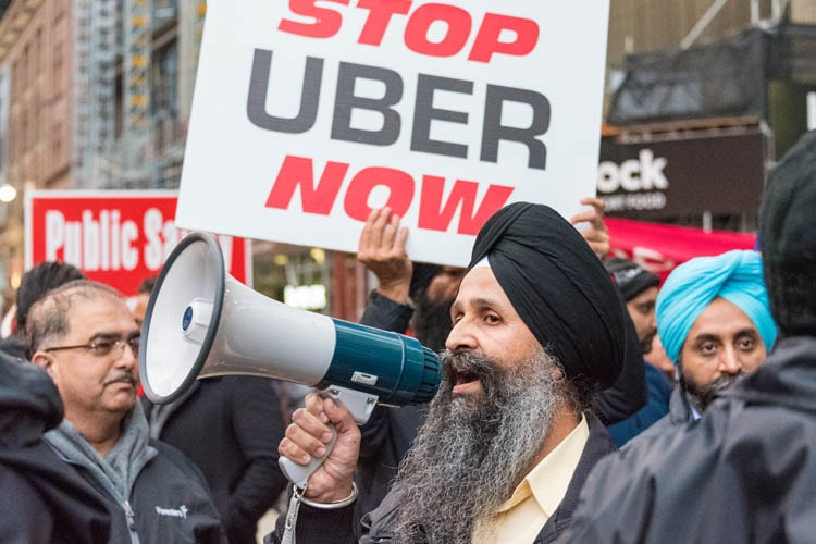 Taxi driver with megaphone protesting against Uber