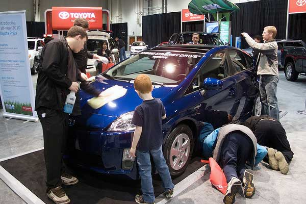 photo of people checking out a Prius car at auto show