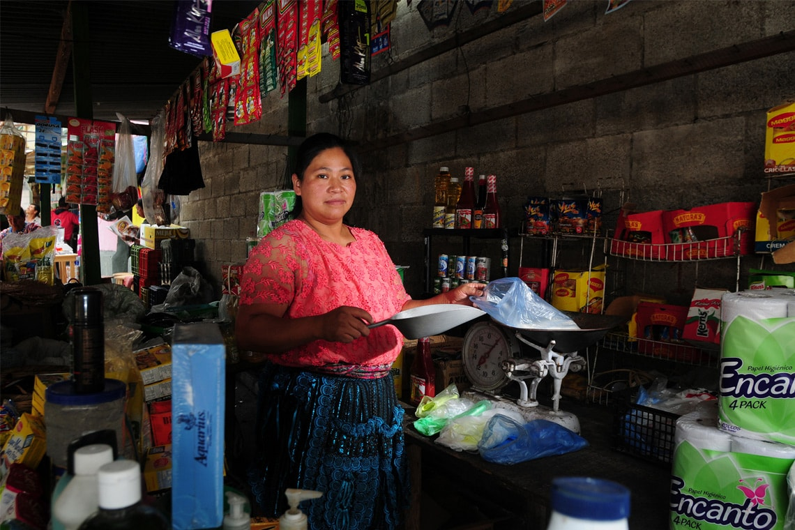 Photo of woman scooping out food at a produce market in Guatemala