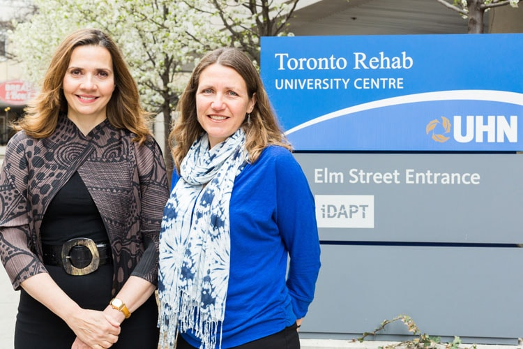 Researchers Margaret Herridge and Jill Cameron stand in front of the University Health Network sign