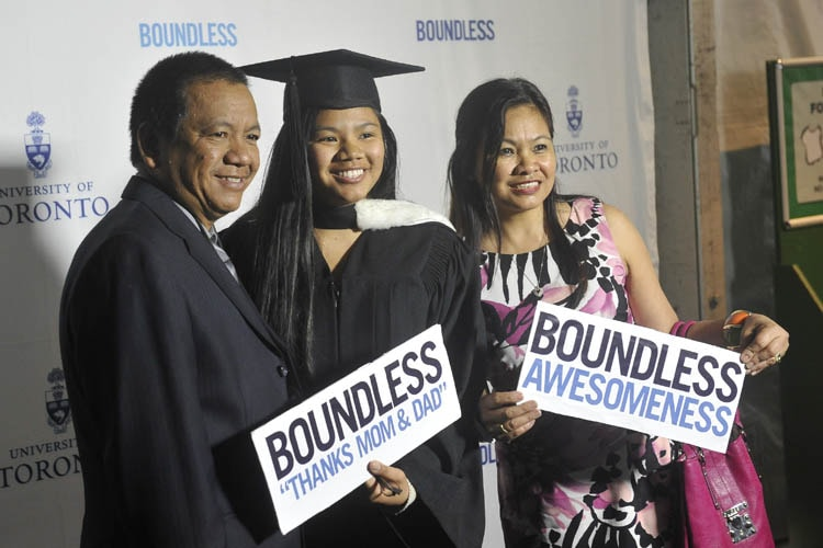 A graduate stands with her parents in the convocation tent