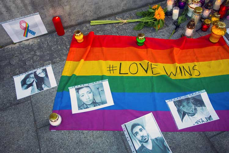 photo of pride flag, candles and flowers outside U.S. embassy in Warsaw