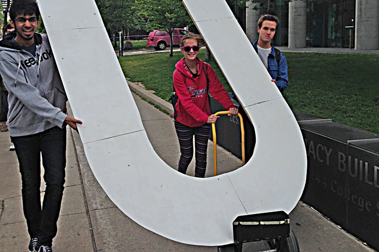Three students carry a giant letter U
