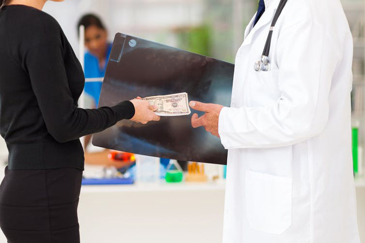 stock photo of doctor taking money from a patient