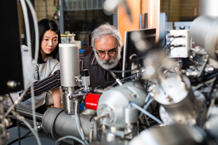 Student and professor examine a mass spectrometer