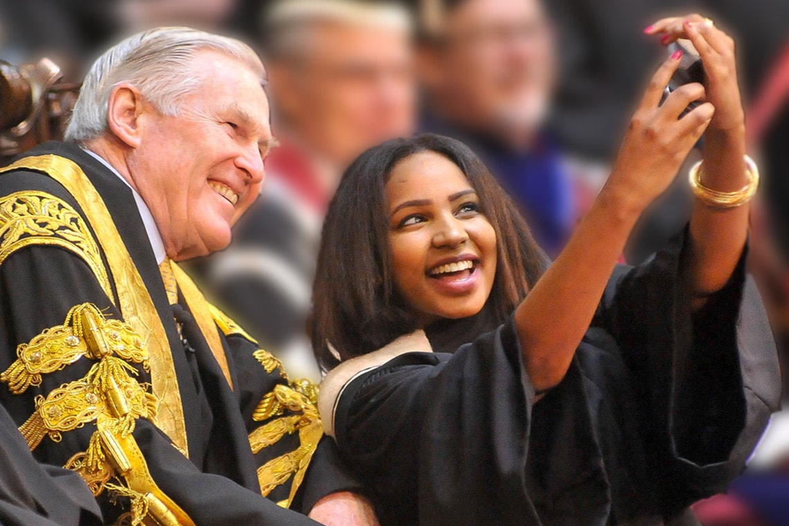 a student takes a selfie with chancellor michael wilson