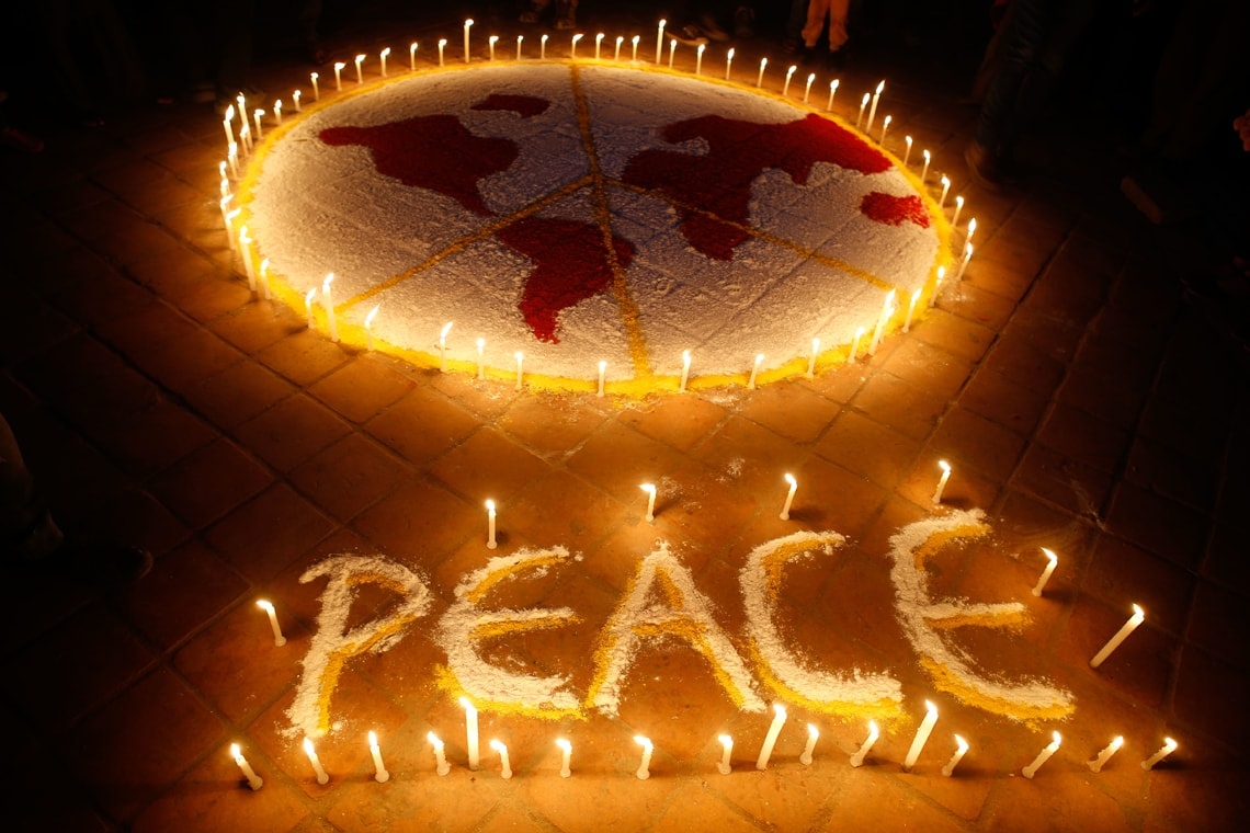 photo of a peace sign written in candles and a drawing of the world