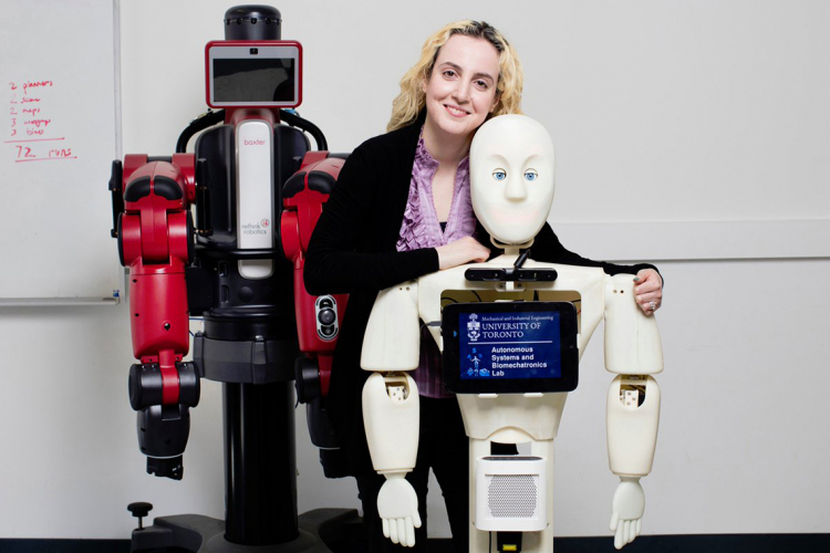 Goldie Nejat poses with her robots at the robotics institute
