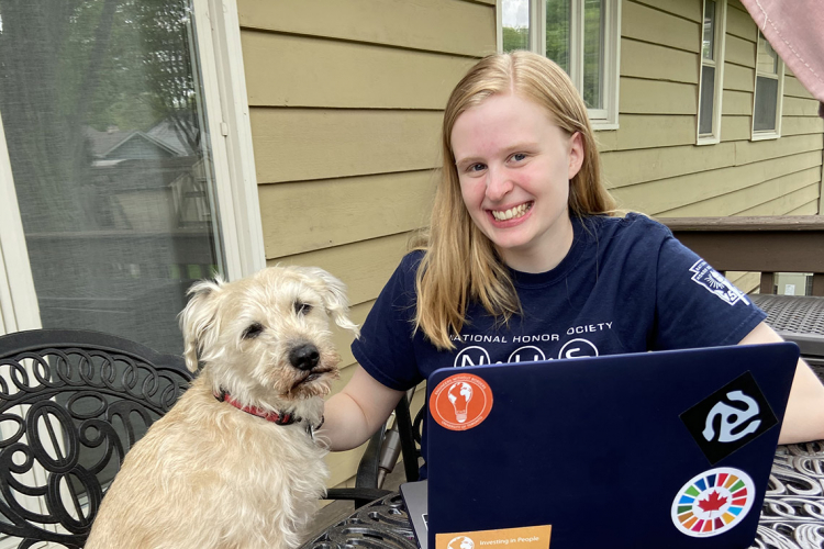 Photo of Lauren Streitmatter working on her computer at home, her dog by her side