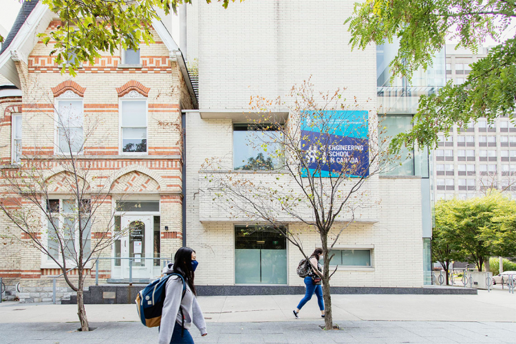 Two students walk past a building at U of T with a sign that says #1 engineering school in canada
