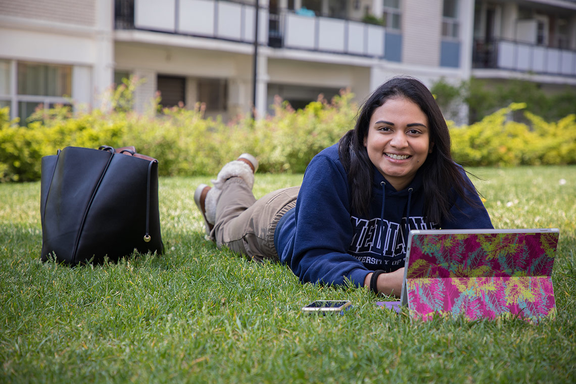 Amanda Khan lies on the grass with her laptop in front of her