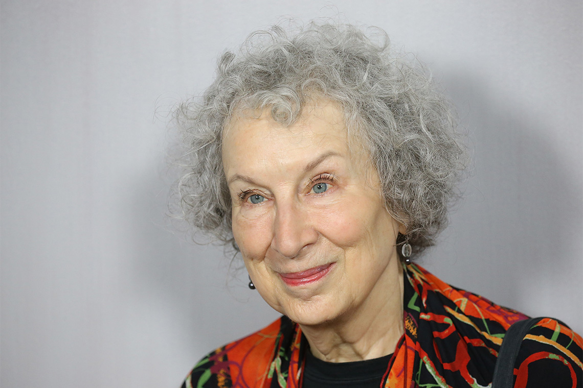 Portrait of Margaret Atwood in front of a grey wall