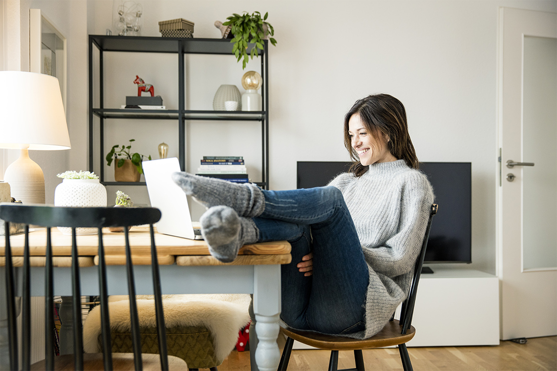 young woman with feet up on desk smiling while talking to someone on her laptop