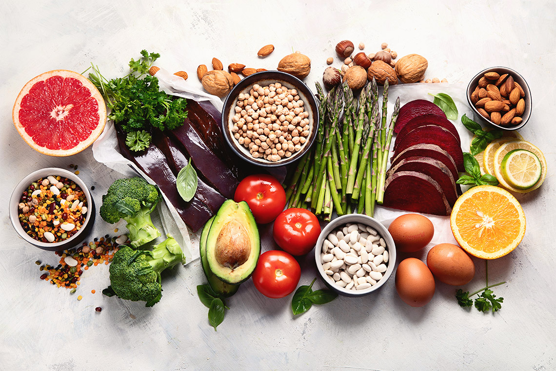 collection of foods high in folic acid including grapefruit, liver, avocado, asparagus, broccoli and nuts