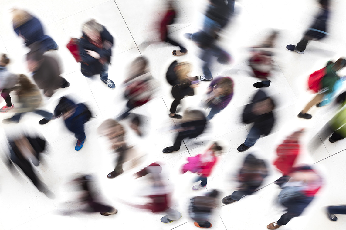 a bluryr overhead shot of a crowd of people moving about while on cell phones