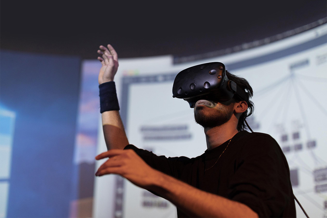 A man using VR goggles in a darkened room