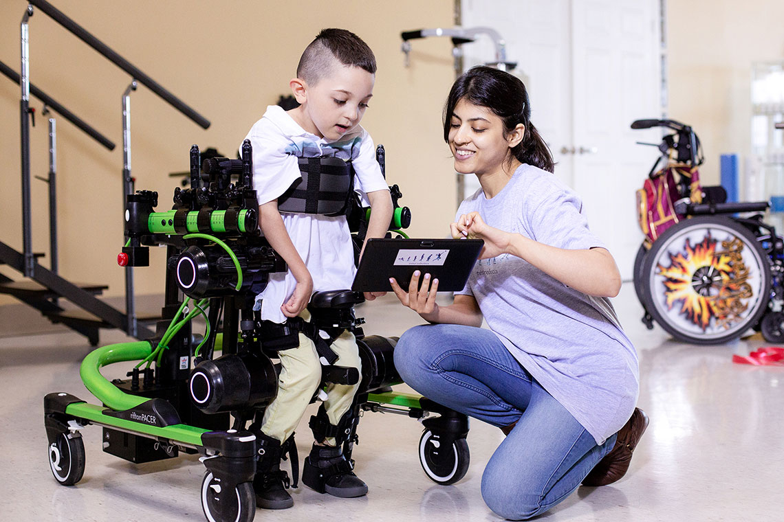A small boy wearing Trexo Robotics assistive technology smiles as a helper shows him a tablet display