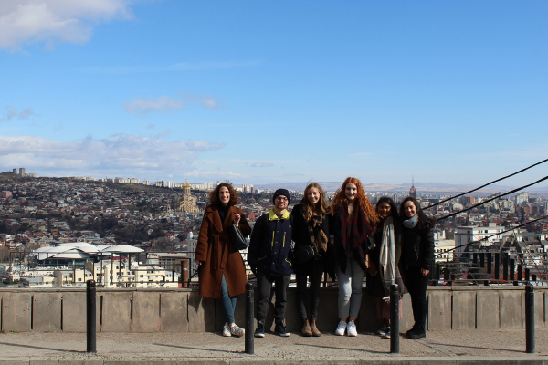 A group of students in the ICM program pose on a hilltop overlooking Tibilisi