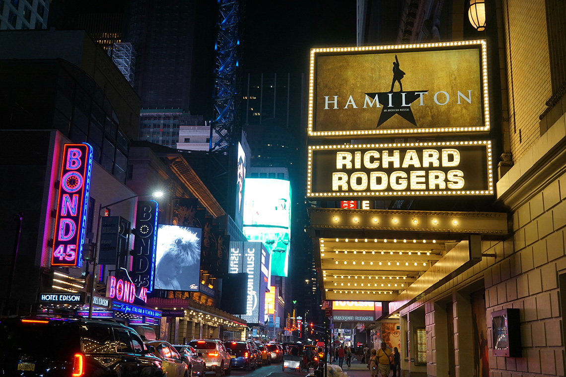 Broadway at night with a marquee for Hamilton in the foreground