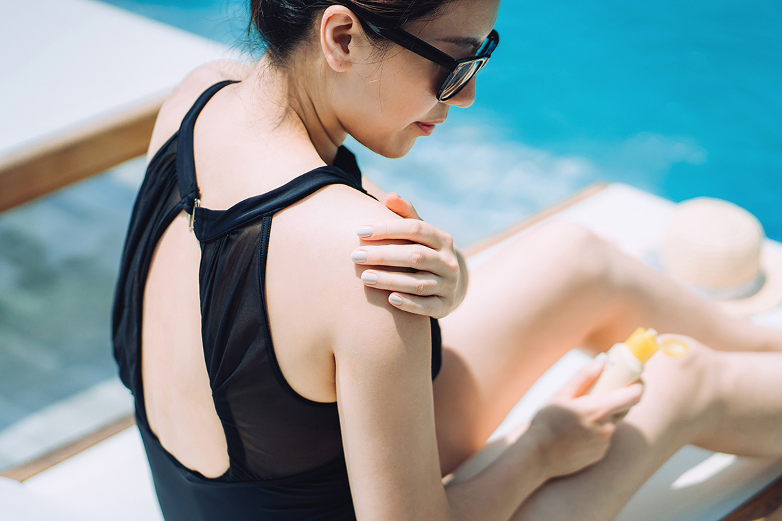 Young woman applies sunscreen by a pool