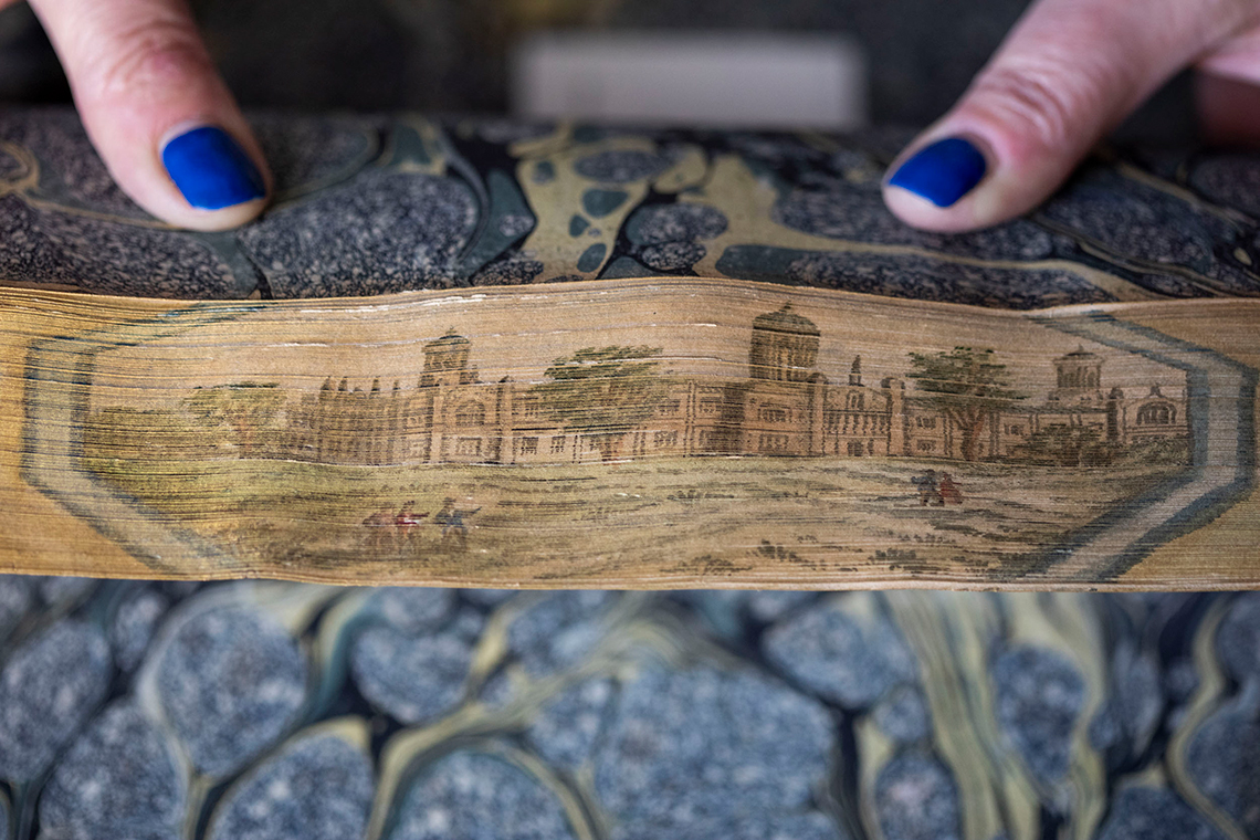 A fore-edge painting book's pages are fanned back to reveal an intricate illustration